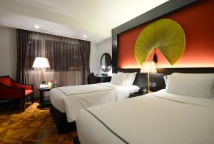 A bed or beds in a room at La Belle Vie Hotel