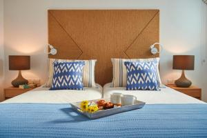 A bed or beds in a room at Louis Nausicaa Luxury Villas