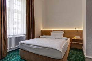 A bed or beds in a room at Hotel Hofgut Sternen