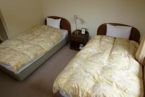 A bed or beds in a room at Little Forest Inn Nikko