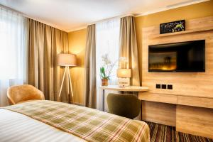 A bed or beds in a room at Leonardo Royal Edinburgh Haymarket