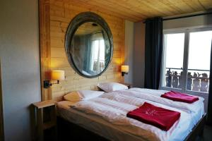 A bed or beds in a room at Le Coucou Hotel & Restaurant-Bar