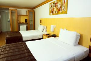 A bed or beds in a room at Planalto Bittar Hotel e Eventos