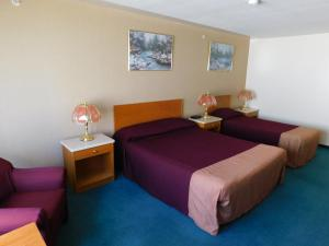 A bed or beds in a room at Western Budget Motel #1 Leduc/Nisku