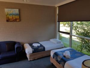 A bed or beds in a room at Motel Traralgon