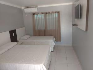 A bed or beds in a room at Hotel Serra do Rio