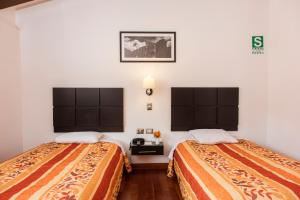 A bed or beds in a room at Hostal El Triunfo