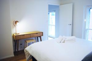 A bed or beds in a room at Canvas Suites on Wills