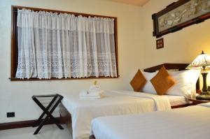 A bed or beds in a room at Sophia's Garden Resort
