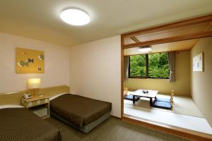 A bed or beds in a room at Park Hotel Miyabitei