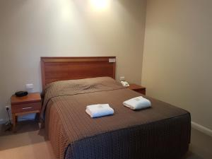 A bed or beds in a room at Vine Inn Barossa