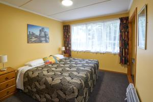 A bed or beds in a room at Accommodation Fiordland Self Contained Cottages