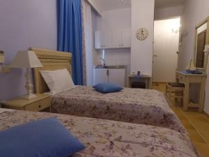 A bed or beds in a room at Akrotiri Hotel