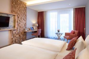 A bed or beds in a room at Dorint Resort & Spa Bad Brückenau