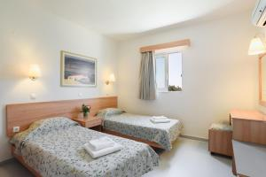 A bed or beds in a room at Matina Pefkos Aparthotel