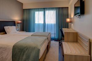 Cama o camas de una habitación en VIP Executive Zurique Hotel