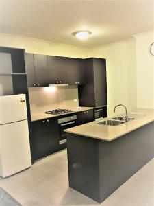 A kitchen or kitchenette at Insaa Serviced Apartments Dandenong