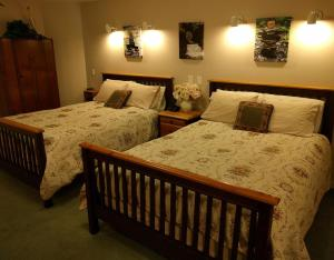 A bed or beds in a room at Cedar Wood Lodge Bed & Breakfast Inn
