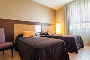 A bed or beds in a room at Hotel Ciudad de Alcañiz