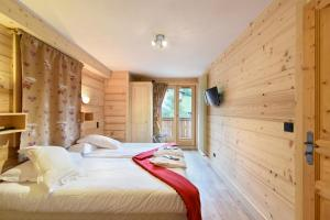 A bed or beds in a room at Loc'Hotel Alpen Sports