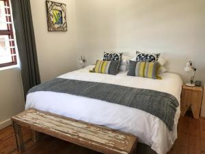A bed or beds in a room at The Cove Guesthouse, Mossel Bay