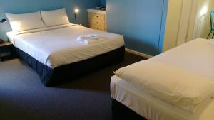 A bed or beds in a room at Blue Pacific Swansea