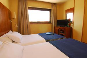A bed or beds in a room at Hotel Galaico