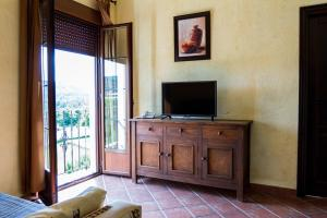 A television and/or entertainment center at Aparthotel Rural 12 Caños