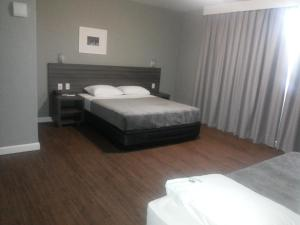 A bed or beds in a room at Duque Center Hotel Residence