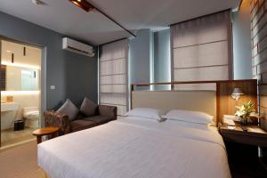 A bed or beds in a room at The Link Yangon Boutique Hotel