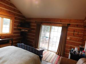 A bed or beds in a room at Riverside Meadows Cabins