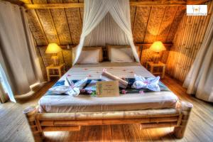 A bed or beds in a room at Bambu Cottages