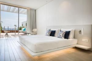 Tempat tidur dalam kamar di Mykonos Dove Beachfront Hotel