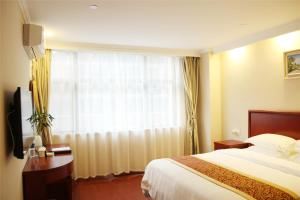 A bed or beds in a room at GreenTree Inn Hebei Tangshan Ring Road South Ring and Fuxing Road Express Hotel