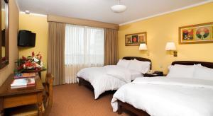 A bed or beds in a room at La Hacienda Miraflores