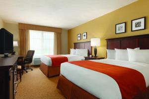 A bed or beds in a room at Country Inn & Suites by Radisson, Pineville, LA