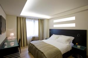 A bed or beds in a room at O&B Athens Boutique Hotel