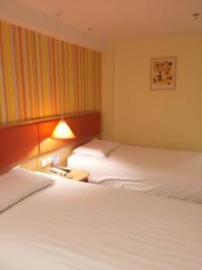 A bed or beds in a room at Hanting Shanghai Pudong Airport Chenyang Road