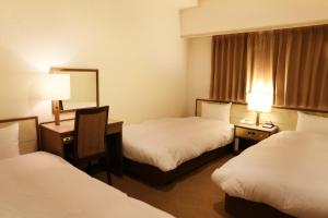A bed or beds in a room at Sun Hotel Nagoya Nishiki