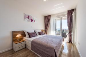 A bed or beds in a room at Apartments with pool Villa Zora