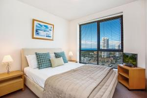 A bed or beds in a room at Mantra Broadbeach on the Park