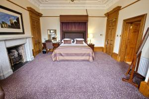 A bed or beds in a room at The Grange Manor