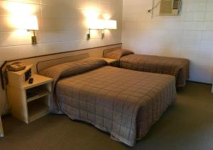 A bed or beds in a room at Cairns Motor Inn