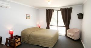 A bed or beds in a room at Deniliquin Golf Leisure Resort