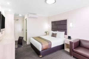 A bed or beds in a room at Garden City Hotel, Best Western Signature Collection