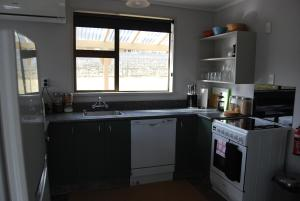 A kitchen or kitchenette at Judge Rock Exclusive Vineyard Cottage Accommodation