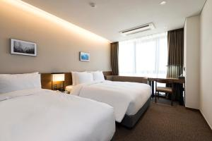 A bed or beds in a room at Ramada Encore by Wyndham Busan Haeundae