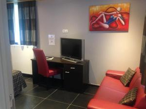 A television and/or entertainment center at AppartHotel Belle Vue