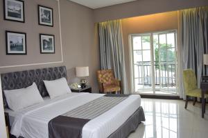 A bed or beds in a room at The Mirah Bogor