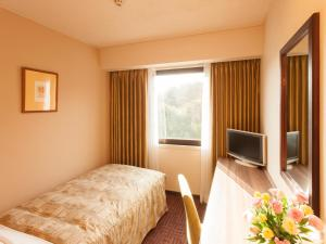 A bed or beds in a room at Hotel Pearl City Kesennuma